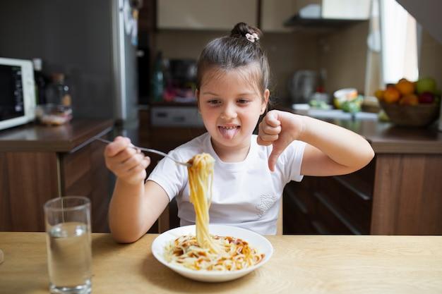 Menina não gosta de prato de massa Foto gratuita