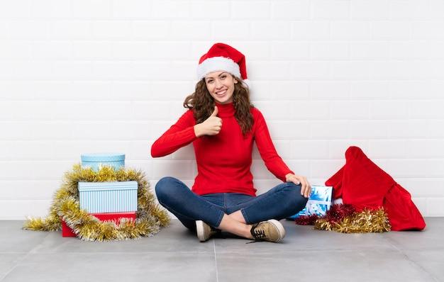 Menina nas férias de natal, sentada no chão, dando um polegar para cima gesto Foto Premium