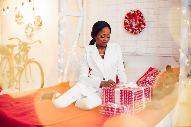 Menina negra elegante na sala de natal decorada Foto gratuita