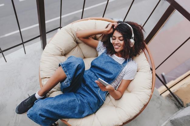 Menina negra satisfeita com tênis da moda, relaxando na cadeira na varanda, curtindo a manhã sozinha Foto gratuita