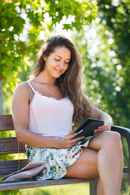 Menina no banco no parque com ereader Foto gratuita