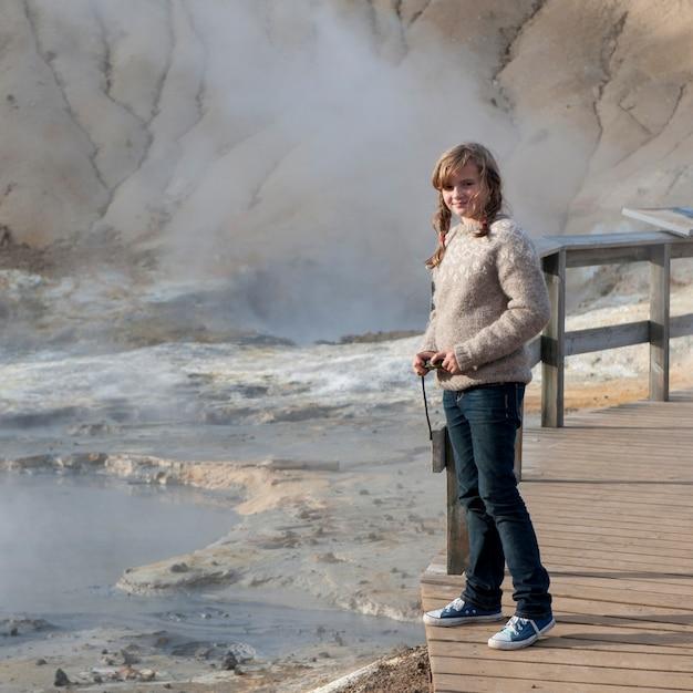 Menina no calçadão ao lado de respiradouros de geyser geotérmica Foto Premium