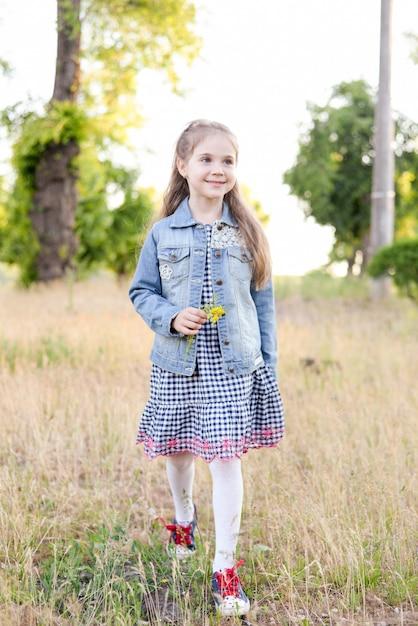 Menina no campo verde durante o dia quente de verão Foto Premium