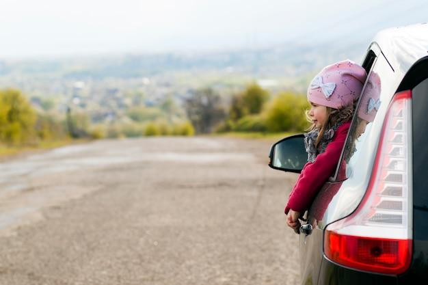 Menina no carro olhando pela janela. Foto Premium