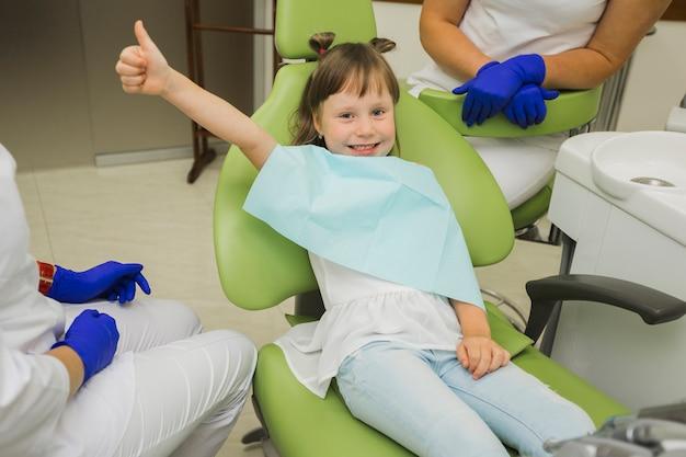 Menina no dentista sorrindo e dando polegares para cima Foto gratuita