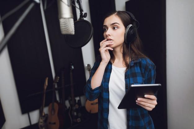 Menina no estúdio de gravação em fones de ouvido. Foto Premium