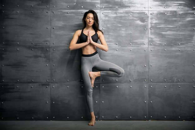 Menina no ginásio fazendo ioga Foto gratuita