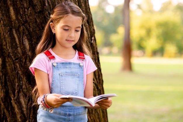Menina no parque lendo um livro Foto gratuita