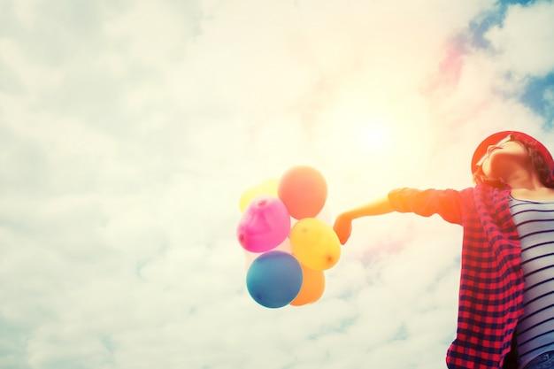 Menina no por do sol com balões Foto gratuita