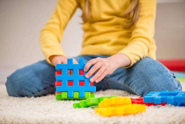 Menina no pulôver amarelo segurando fragmentos de lego. Foto Premium