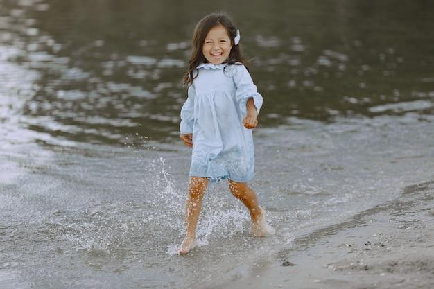Menina no rio. menina espirra água. menina de vestido azul. Foto gratuita