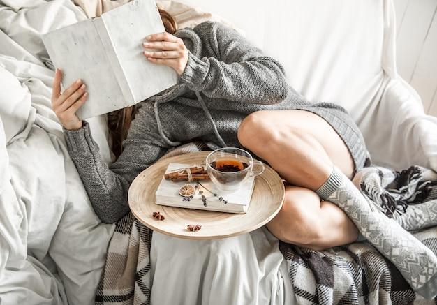Menina no sofá com chá e um livro Foto Premium