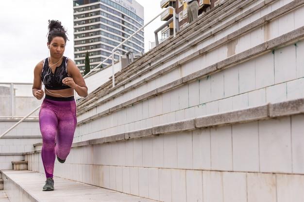 Menina no sportswear correndo pela cidade Foto Premium