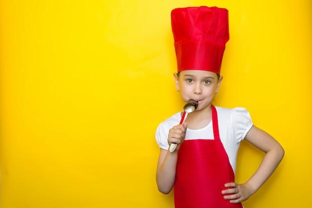Menina no terno de um chef vermelho lamber a colher, sabor delicioso Foto Premium
