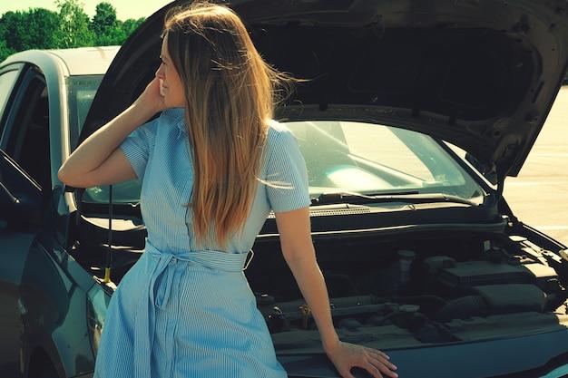 Menina nova e bonita perto de um carro quebrado com uma capa aberta. problemas com o carro, não inicia, não funciona. Foto Premium