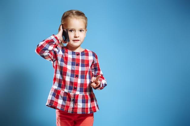 Menina ocupada falando no telefone móvel em fundo azul Foto Premium