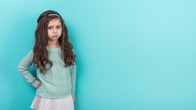 Menina ofendida segurando a mão na cintura Foto gratuita