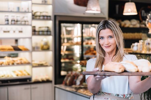 Menina, oferecendo, bandeja pão Foto gratuita