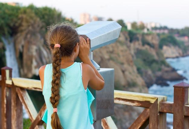 Menina olhando através de binóculos para o mar mediterrâneo Foto Premium