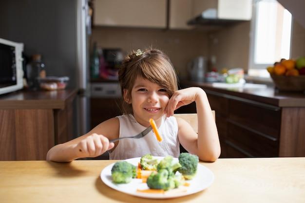 Menina olhando para a câmera enquanto come legumes Foto gratuita