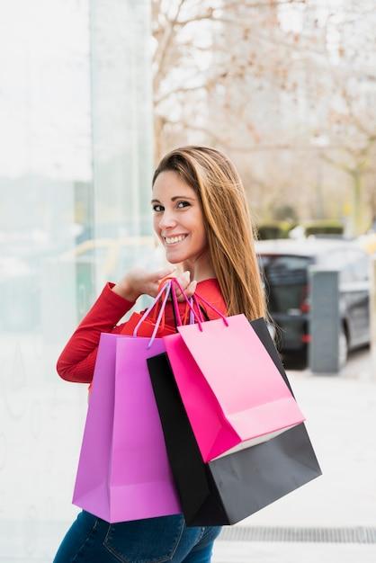 Menina olhando para a câmera enquanto segura sacolas de compras Foto gratuita