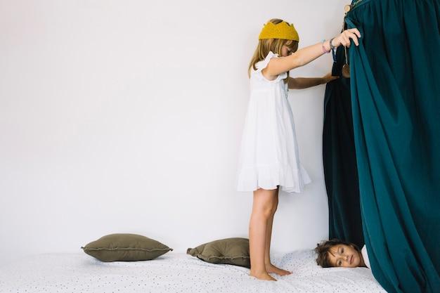 Menina olhando para a irmã atrás das cortinas Foto gratuita