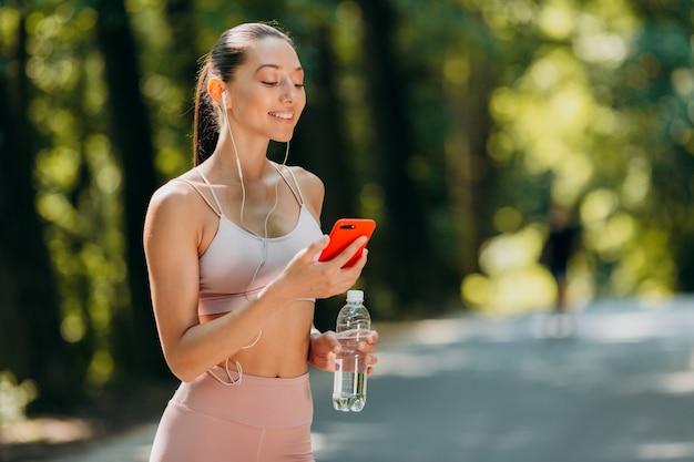 Menina olhando para a tela no smartphone e ouvir música em fones de ouvido ao ar livre. Foto Premium