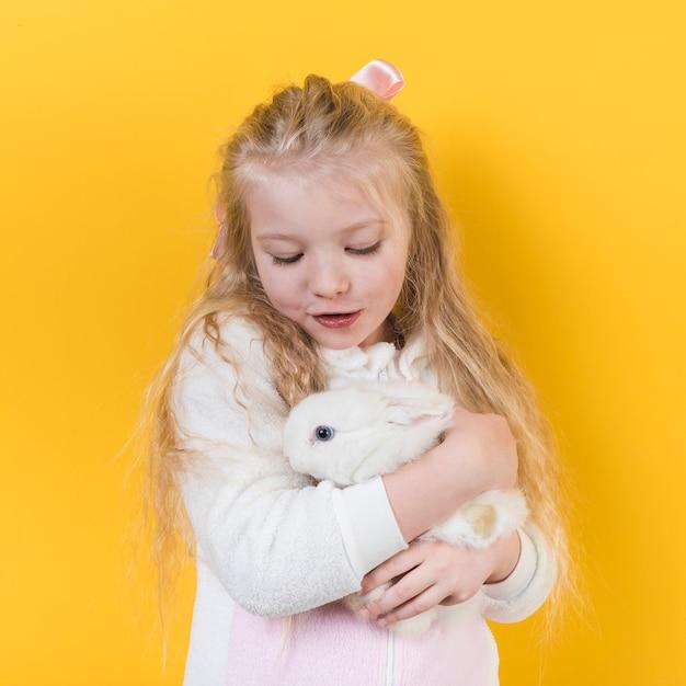 Menina olhando para coelho branco Foto gratuita