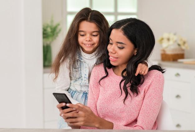 Menina olhando para mãe móvel Foto gratuita