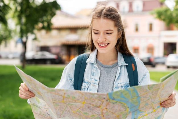 Menina olhando para uma vista frontal do mapa Foto gratuita