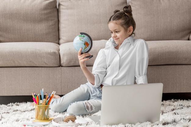 Menina olhando um globo da terra Foto gratuita