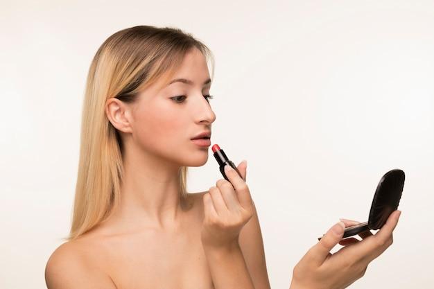 Menina, olhar, em, a, espelho, e, pôr, batom Foto gratuita