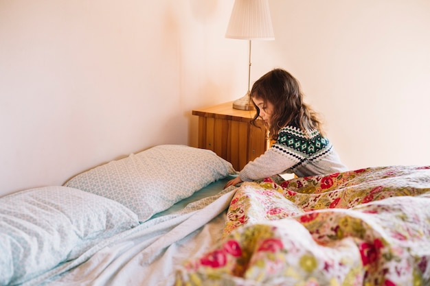 Menina, organizando lençol no quarto Foto gratuita