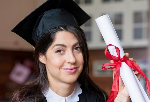 Menina orgulhosa com seu diploma Foto gratuita