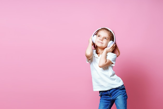 Menina ouvindo música em fones de ouvido. filho bonito, desfrutando de música de dança feliz, fechar os olhos e sorrir posando Foto Premium