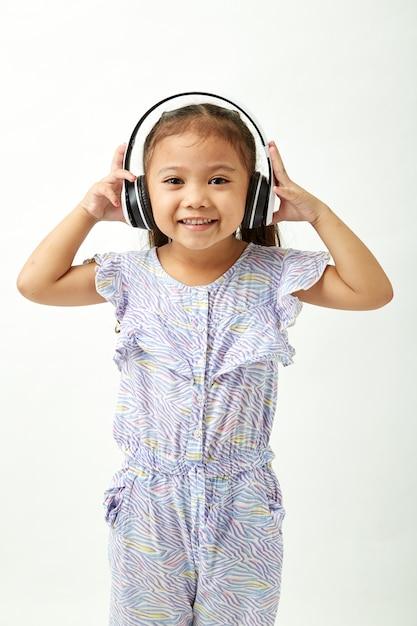 Menina ouvindo música em fones de ouvido Foto Premium