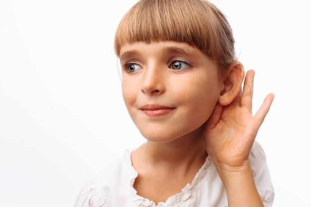 Menina ouvindo na parede branca Foto Premium