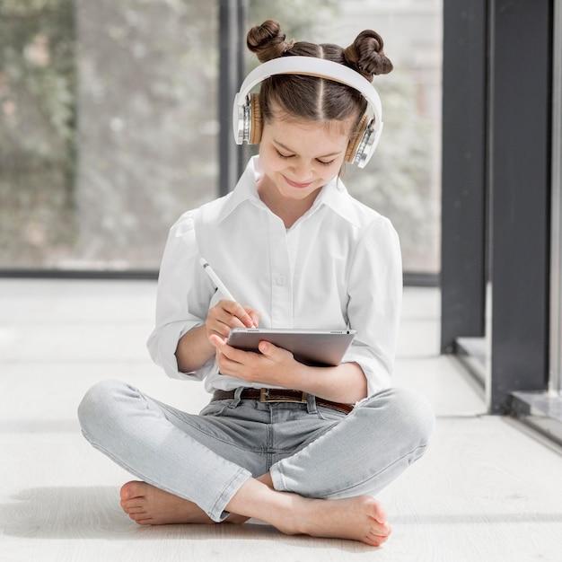 Menina ouvindo seu professor através de fones de ouvido Foto gratuita