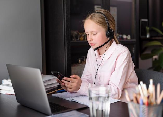 Menina participando de aulas on-line dentro de casa Foto gratuita