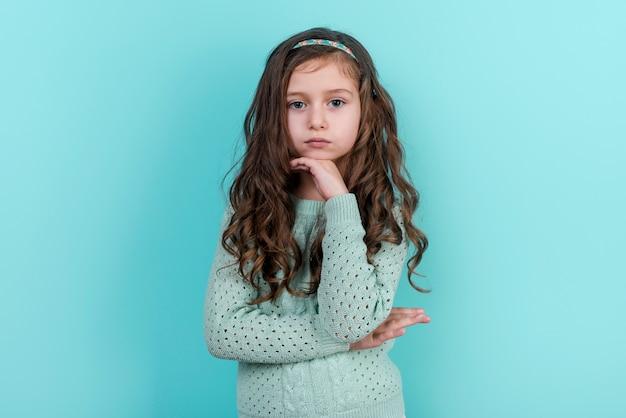 Menina pensativa em pé no fundo azul Foto gratuita