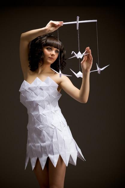 Menina pensativa em um vestido de origami segurando um pássaro de origami nas mãos Foto Premium