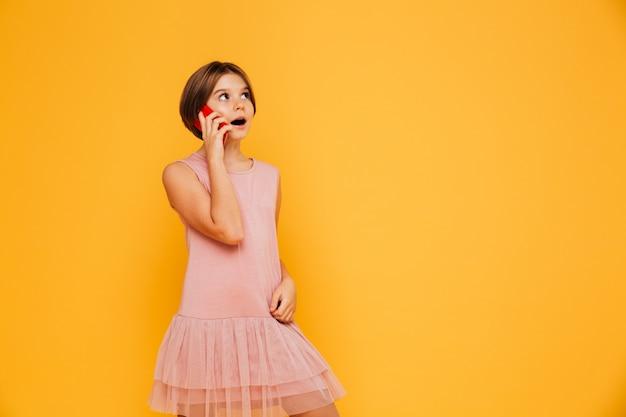 Menina pensativa olhando para o espaço da cópia e falando no smartphone isolado Foto gratuita