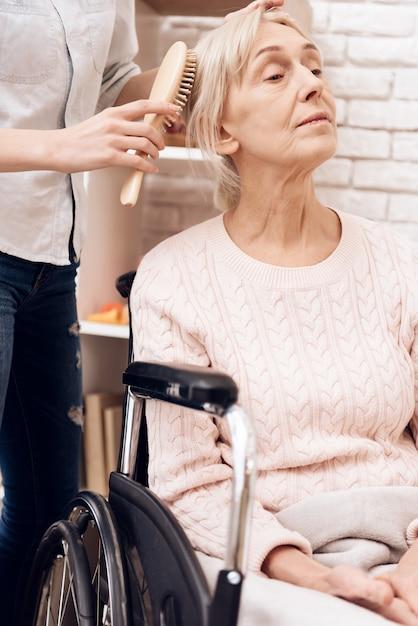 Menina penteando uma mulher idosa em casa Foto Premium