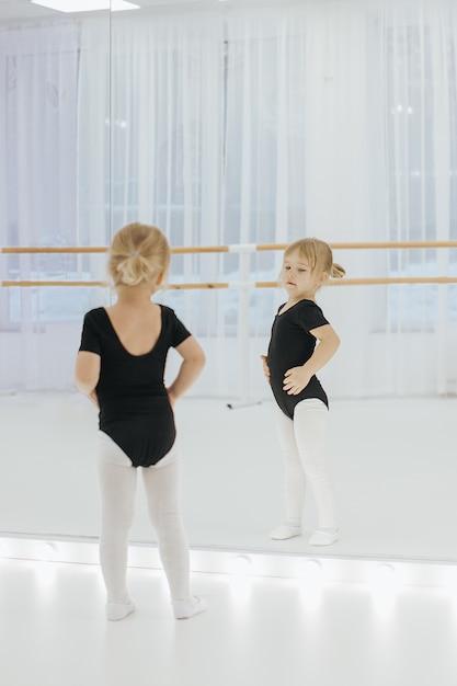 Menina pequena da bailarina no preto. criança adorável que dança o bailado clássico. dança das crianças. crianças realizando. dançarino dotado novo em uma classe. pré-escolar garoto tendo aulas de dança. Foto Premium