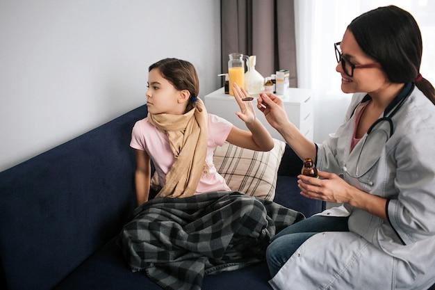 Menina pequena doente não quer tomar xarope. ela olha para a parede e segura a mão perto da colher. médico feminino jovem alegre olhar para paciente e sorrir. ela segura a colher com calda. Foto Premium