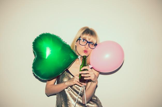 Menina posando com balões e cerveja Foto gratuita