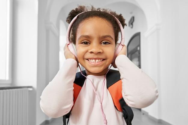 Menina positiva usando fones de ouvido rosa grandes Foto Premium