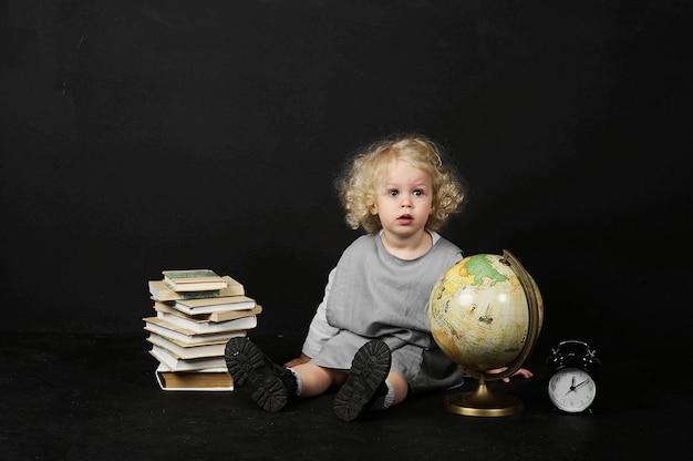 Menina pré-escolar feliz com livros, globo e relógio em um fundo preto Foto Premium