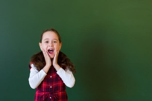 Menina pré-escolar feliz estudante em vestido xadrez em pé na classe perto de um quadro negro verde. Foto Premium