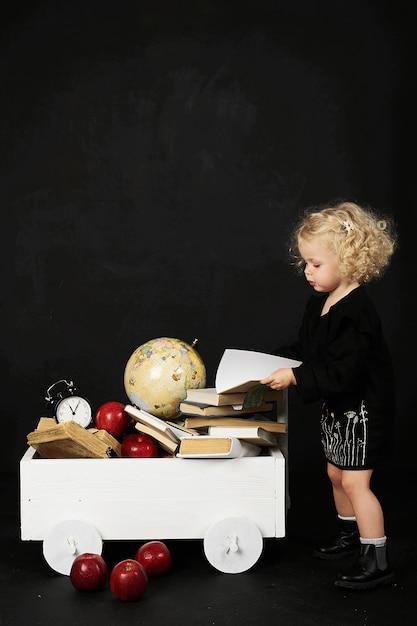 Menina pré-escolar feliz perto do carrinho com livros, globo e relógio em um fundo preto Foto Premium